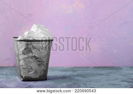 A trash can for paper. Beautiful pink background with place for text. A full trash can for crumpled paper sheets.