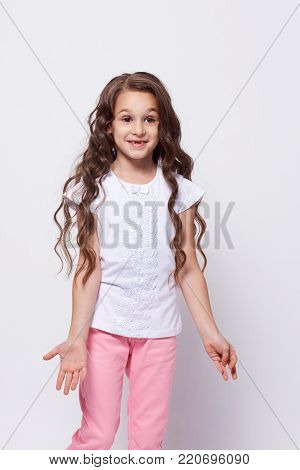 Little girl. Bewilderment. Emotions misunderstanding. Gray background