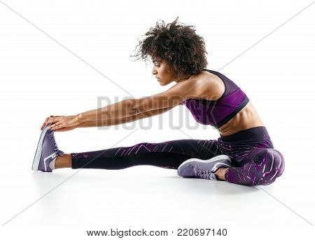 Sporty girl stretching her hamstrings. Photo of african girl doing exercising on white background. Sports