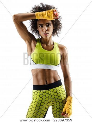 Boxer wiping off the sweat from her face. Photo of young african girl isolated on white background. Strength and motivation