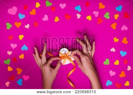 Valentines day gift wrapping with boxes over pink background and colorful paper hearts around. Process of handmade Present. Creative diy craft hobby. Holiday decorations