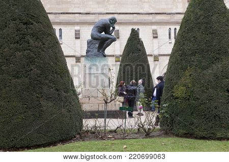 Paris, 30 december 2017: tourists take photographs of statue thinker by Rodin in garden of museum rodin