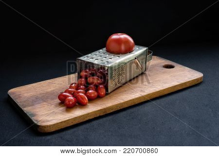 Culinary concept Preparation recipe tomato juice. Large tomato and old grater down to small grape cherry. Low calorie food.