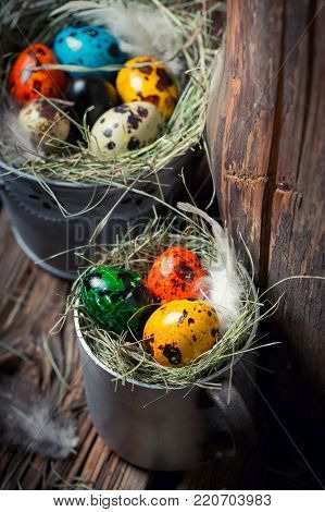 Colourfull eggs for Easter on hay on wooden background