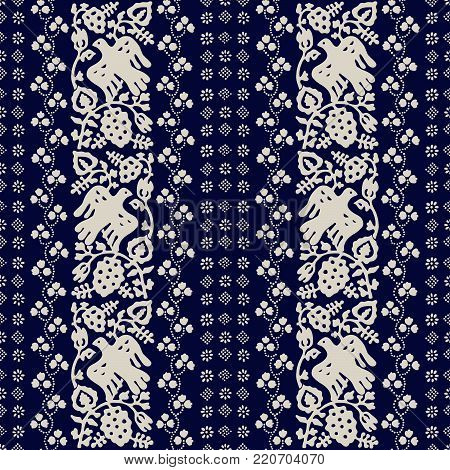 Block printed seamless floral pattern. Ethnic Russian folk motif with birds, vine, clover ornament and flower blocks. Ecru on  blue background Textile print.
