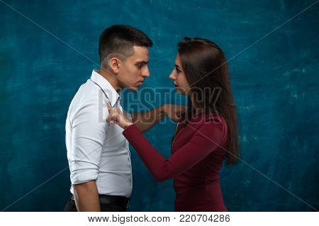 Young couple in conflict. Woman and man swear looking at each other and touching by finger against blue background