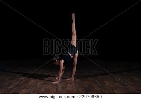Girl gymnast doing gymnastic sports exercises on a black background. Sport