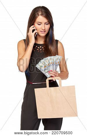 Woman holding paper shopping bag with blank copy space for text and cash US dollars talking on mobile phone concentrated, over white background