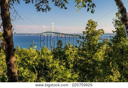 Summer Vacation At Mackinaw. View of the Mackinac Bridge framed by the forest of the Upper Peninsula with the blue waters of Mackinaw at the horizon. St. Ignace, Michigan.