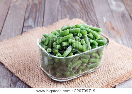 Frozen string beans in a glass box on a wooden table