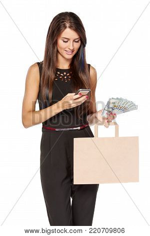Woman holding paper shopping bag with blank copy space for text and cash US dollars using mobile phone, over white background