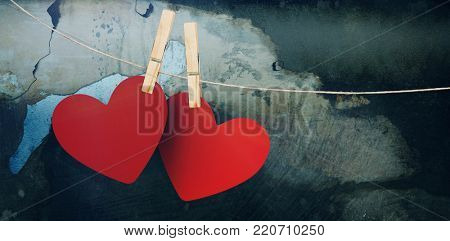Hearts hanging on line against rusty weathered wall