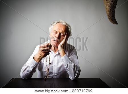 Old man is praying with wooden rosary beads and devil as snake. Prayer and temptation concept.