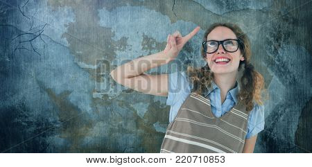 Geeky hipster woman pointing up  against rusty weathered wall