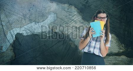 Geeky hipster hiding her face behind notepad  against rusty weathered wall