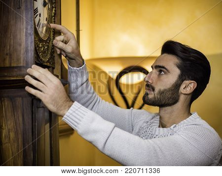 Side view of young handsome man standing and setting vintage pendulum clock.