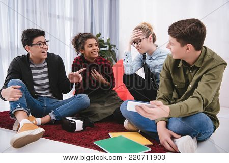 young laughting teenagers sitting on carpet, studying and pointing on girl
