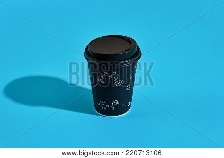Hot coffee in black paper cup with black lid on blue background with shadow, blurred and soft focus image. Still life. Copy space