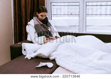 sad young girl sick, sitting in bed under a blanket, round neck warm scarf