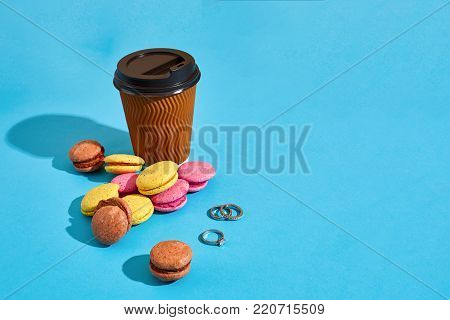 Hot coffee in brown paper cup with black lid and macaroons on blue background with shadow, blurred and soft focus image. Still life. Copy space Valentine's Day