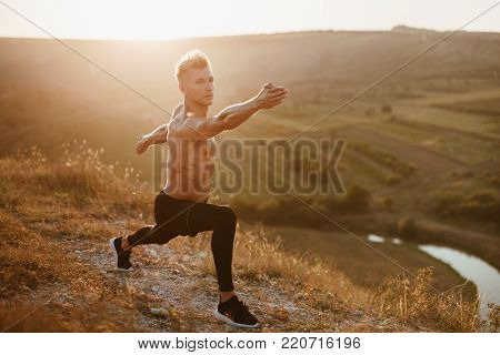 Young shirtless man working out on hill in sunlight training stamina and endurance.