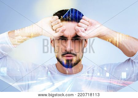 Brutal and masculine. Serious nice determined man looking in front of him and holding his hands up while standing against blue background