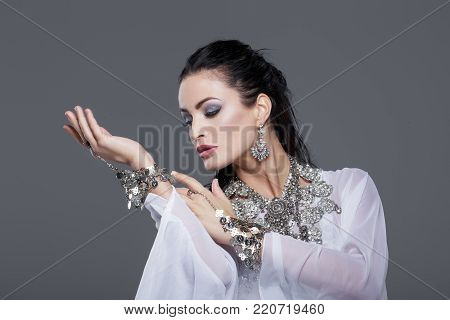 Sensual belly dancer performance portrait on grey background