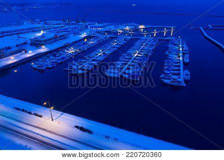 HIdaka, Hokkaido, Japna - 29 December 2017 - The boats dock at night on a cold snowing winter night in the peir of Hidaka, Hokkaido, Japan on December 29, 2017