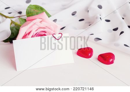 St Valentines day background. Rose, blank love card and two heart shaped candies. Romantic St Valentine's Day still life with blank card for St Valentine's Day message. St Valentine's Day festive background