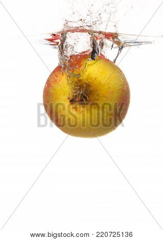 Yellow red apple in the water splash isoated on white background. Healthy organic food and active life.