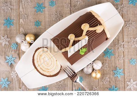 Chocolate yule log cake with Christmas decorations disposed on wooden table. View directly from above.