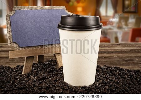 Cup of coffee and coffee beans on an old wooden table in a restaurant, dining room in the background.