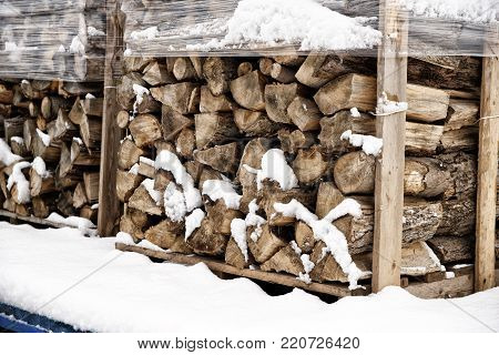 Stack of chopped firewood, covered in winter snow. Wood cut and drying, ready to burn in fireplace.