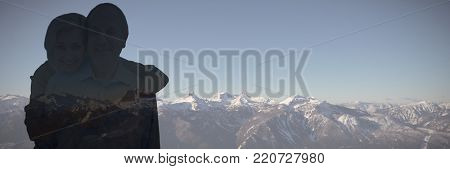 Happy mature couple embracing smiling at camera against snow covered mountains against clear sky