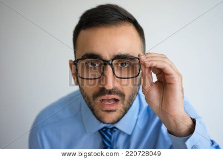 Closeup portrait of surprised handsome young man staring at camera through glasses. Surprise concept. Isolated front view on grey background.