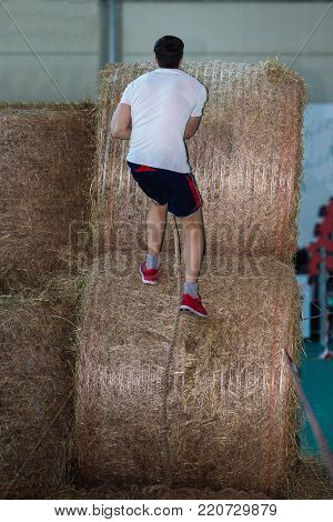 Indoor Hay Bale Obstacle Running Contest: People Climb Bale with Rope.