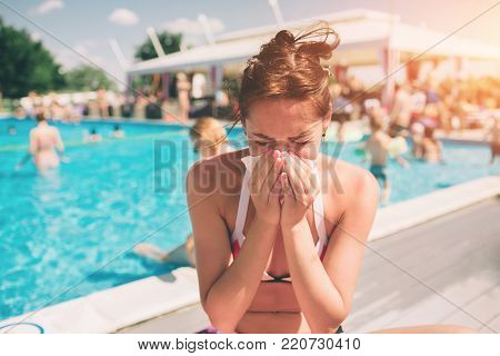 picture from a Beautiful women in bikini with handkerchief. Sick female model has runny nose. girl makes a cure for the common cold. She is sick in the summer on vacation