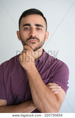 Closeup portrait of thoughtful young man looking at camera and touching chin. Contemplation concept. Isolated front view on grey background.