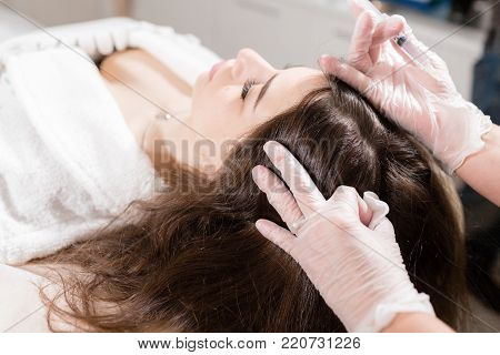 Handsome woman receives an injection in the head. The procedure makes doctor in white gloves. The concept of mesotherapy. Thrust to strengthen the hair and their growth. v