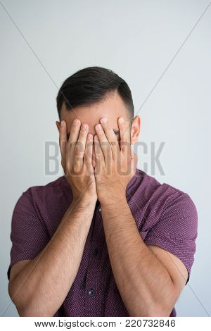 Closeup of young man covering face with hands. Depression concept. Isolated front view on white background.