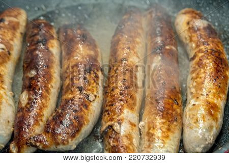 Fried sausages are cooked in the pan