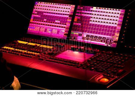 Control panel of mixer with buttons and sliders. Professional stage lights lighting control and mixing equipment for clubs live events, concerts glowing in purple pink colors on black background