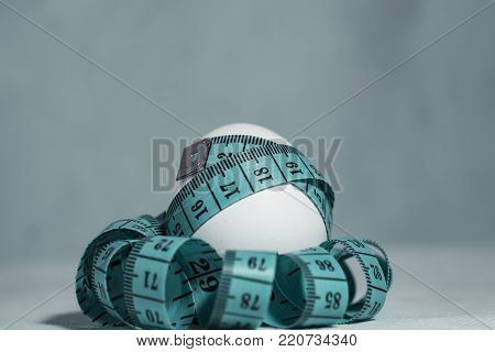 Symbol of diet and excess weight or obesity. White chicken egg girded with a blue tape of tape measure. Close-up.