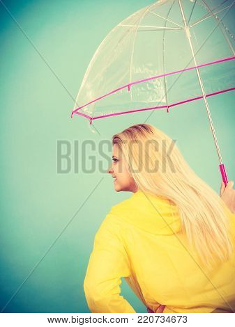 Rainy autumn day accessories ideas concept. Blonde woman wearing raincoat holding clear transparent umbrella, back view.