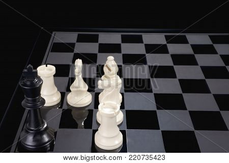 A chess king in checkmate cornered by five other pieces.