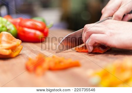 cooking. close up of male hand cutting pepper on cutting board at home. stock photo
