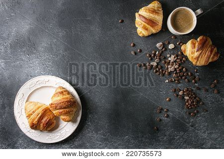 Fresh baked traditional croissants on white vintage plate and mug of espresso coffee, coffee beans, sugar over black texture background. Top view, copy space
