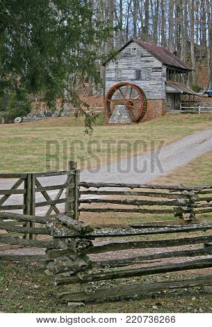 an old gristmill with a rusty wheel, behind a split-rail fence