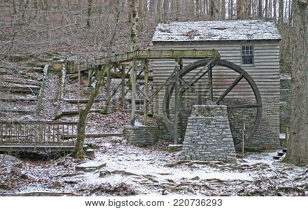 an old gristmill with a light dusting of snow