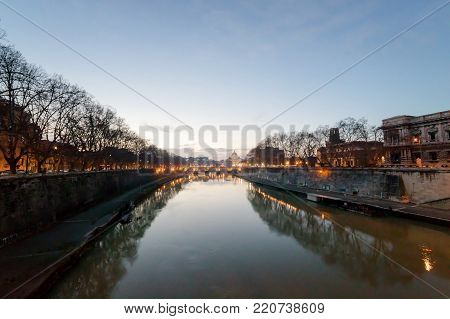 The Tiber river and in the background San Pietro, in a panoramic photograph at sunset.